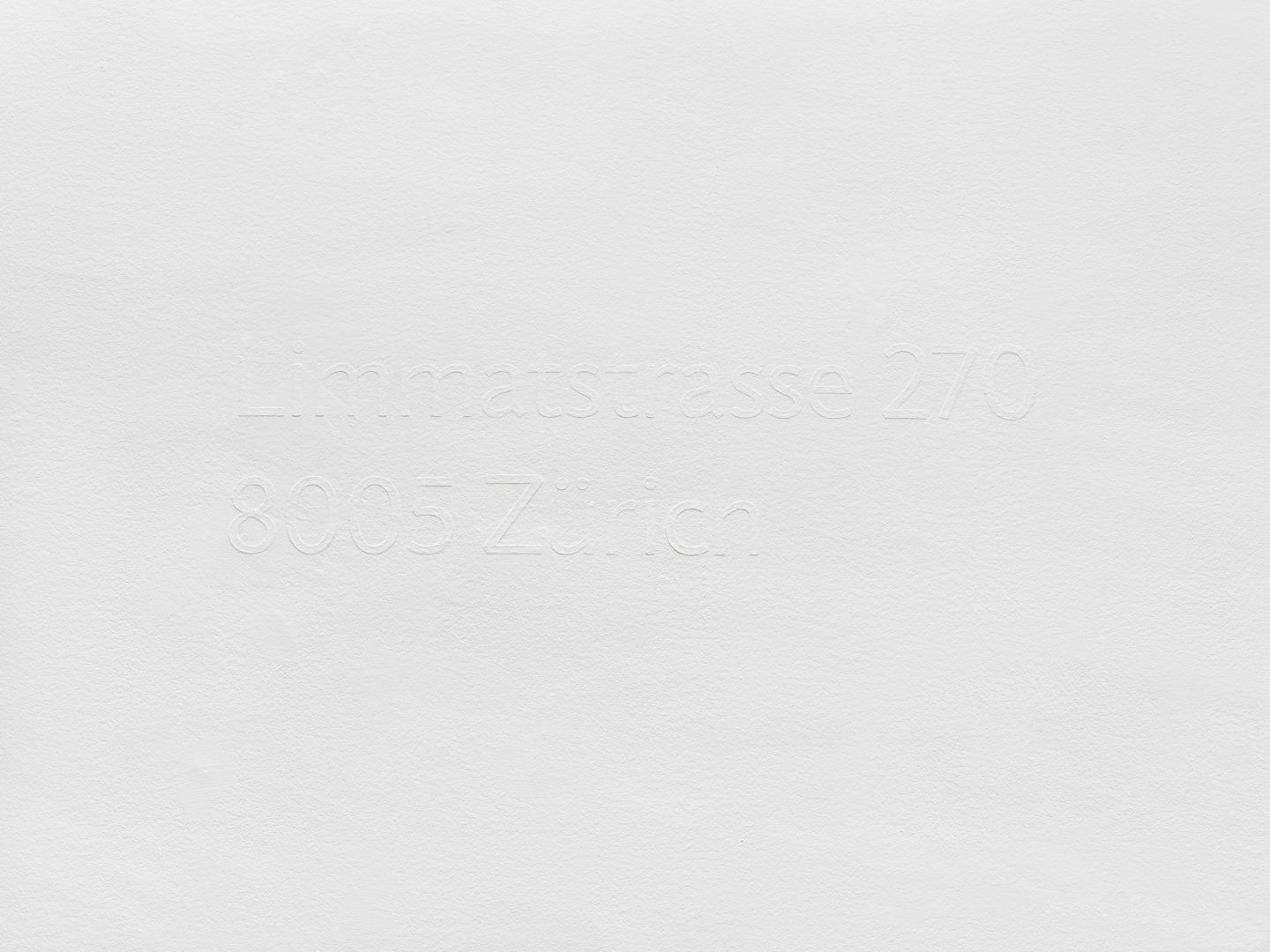 Maria Eichhorn, Limmatstrasse 270, 8005 Zürich (2011/2018), postal address, wall text, bas-relief, white emulsion paint on a white wall, manual application of paint with a brush in multiple layers, typeface: Jigsaw Regular, Dimensions variable, here: 27 x 98,3 cm, Wall painting: Christian Eberhard, Sammlung Migros Museum für Gegenwartskunst, photo: Stefan Altenburger Photography, Zurich © ProLitteris, Zürich
